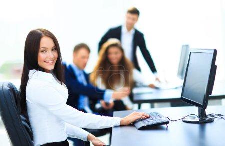 Heureuse jeune femme d'affaires regardant derrière et ses collègues travaillent