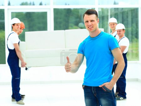 Photo for Happy male movers in uniform carrying white sofa - Royalty Free Image