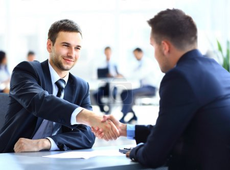 Photo for Two business colleagues shaking hands during meeting - Royalty Free Image