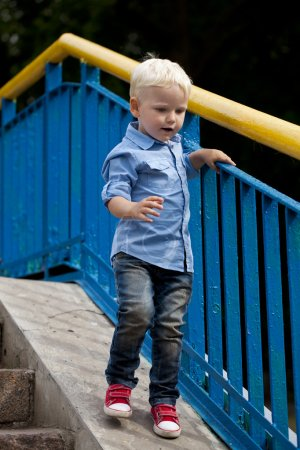 Blonde baby boy in  blue shirt and jeans