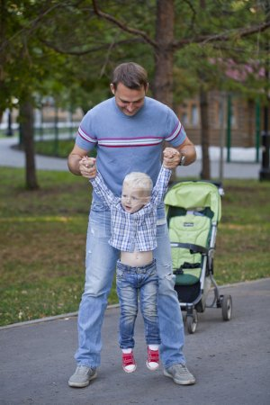 Father with two year old son in summer park