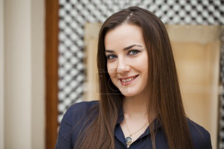 Portrait of young brunette model posing in shop