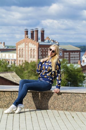 Young beautiful woman in blue jeans sitting in summer street par