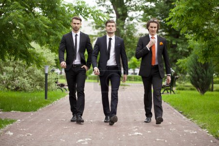 Photo for Three young men in elegant business suits walking in summer street, outdoors - Royalty Free Image
