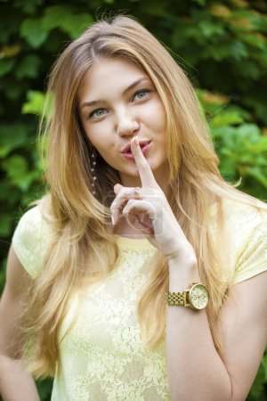 Young beautiful woman has put forefinger to lips as sign of sile