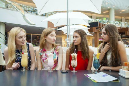 Close up four attractive young women drinking cocktails in shopp