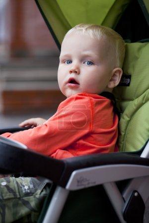Little boy sitting in stroller