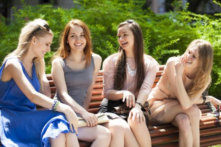 Four Teenage Girls Sitting On Bench In summer Park