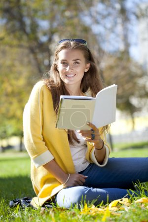 Beautiful schoolgirl sitting in autumn park and reading a book