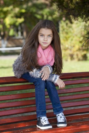 Photo for Beautiful little girl sitting on a bench in autumn park - Royalty Free Image