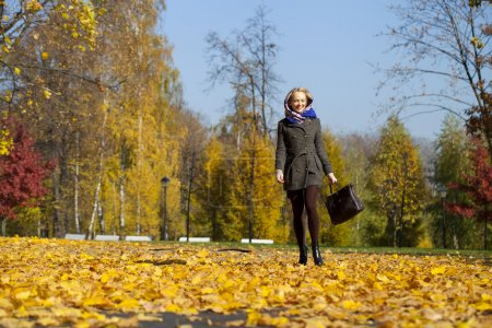 Photo for Full length, walking happy woman in autumn park - Royalty Free Image