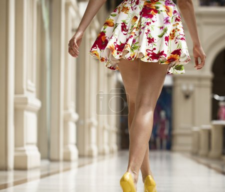 Photo for Beautiful shapely female legs back view in flowers dress in the shop - Royalty Free Image