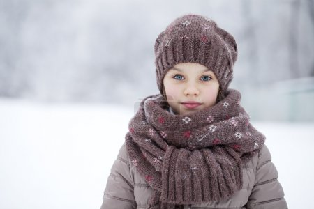 Happy little girl on the background of a winter park