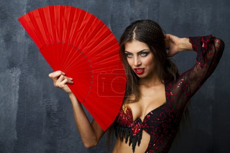 Photo for Sexy Woman traditional Spanish Flamenco dancer dancing in a red dress with fan - Royalty Free Image