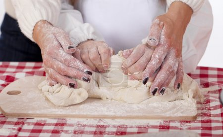 Photo for Caring Hands mother helping her daughter prepare dough - Royalty Free Image