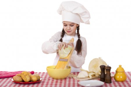 Portrait of a little girl in a white apron and chefs hat shred c