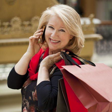 Photo pour Mature femme blonde heureuse avec des sacs à provisions, appelant par téléphone - image libre de droit
