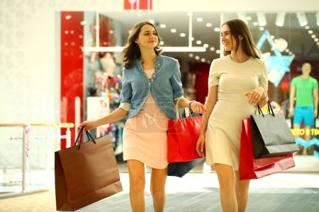 Two young women walking with shopping at the store