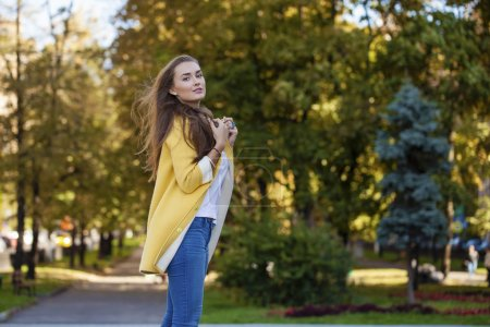 Happy young woman in yellow coat in autumn street