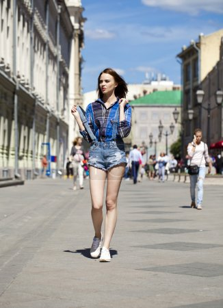 Full length portrait of young beautiful brunette woman in blue j