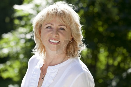 Photo for Close up portrait of lovely middle aged woman in the summer park - Royalty Free Image