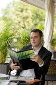 Obchodní mladý muž, který držel menu posezení v letní restauraci