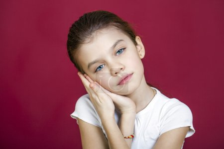 Portrait of a charming brunette little girl looking at camera