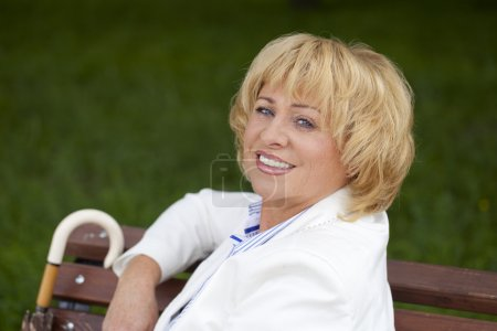 Portrait of lovely middle aged woman in the summer park