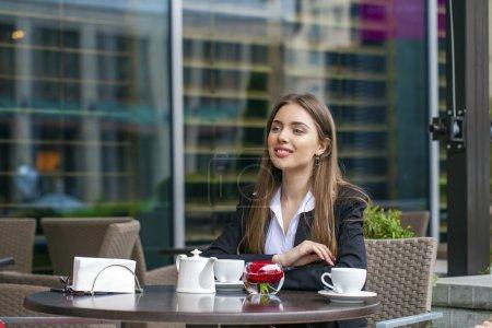 Photo pour Jeune femme d'affaires en buvant une tasse de café dans un café d'été - image libre de droit