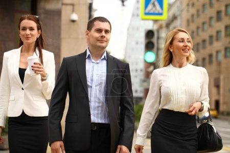 A young businessman walking on the street with their secretaries