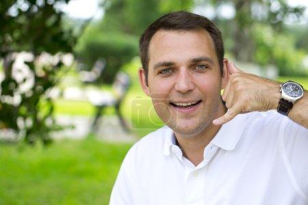 Happy brunette men making a call me gesture