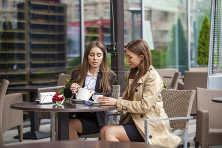 Photo for Two young business women having lunch break together in a coffee shop - Royalty Free Image