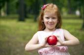 Little red-haired girl holding a red apple on a background of gr