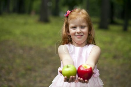 Little red-haired girl in a pink dress holding two apples