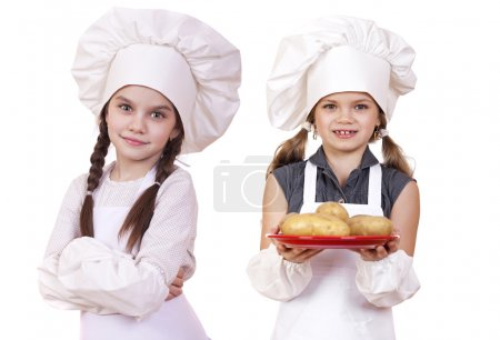 Cooking and people concept - Two Little girls in a white apron