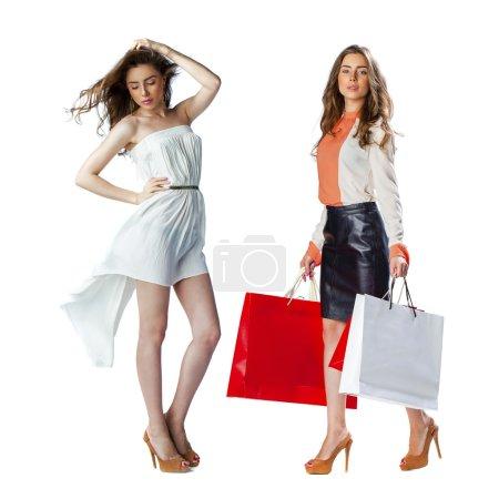 Portrait of a beautiful young brunette women posing with shoppin