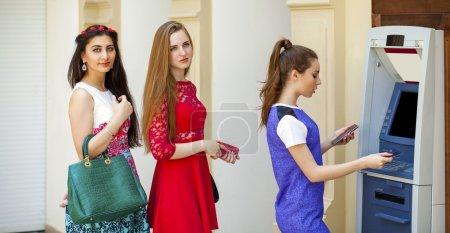 Photo pour Un petit tour à l'Atm, la jeune femme à l'aide d'un distributeur automatique. Femme balance argent ou compte chèques de retrait - image libre de droit