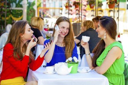 Photo pour Trois jeunes belles filles petite amie boire du thé dans un caf d'été - image libre de droit