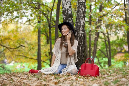 Happy beautiful woman calling by phone sitting in the autumn par