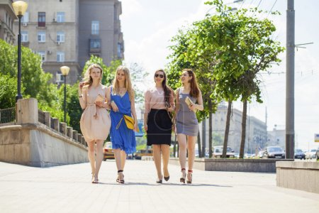 Portrait of a beautiful young four women walk on summer city