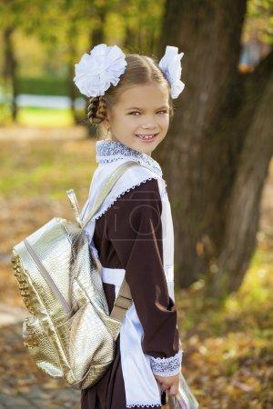Photo pour Portrait d'une belle jeune élève de première année en uniforme scolaire festif sur le fond parc d'automne - image libre de droit