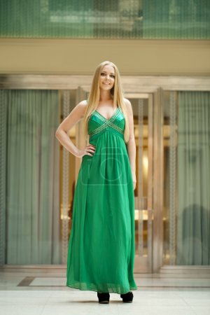 Happy beautiful woman in a long green dress