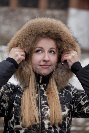 Young beautiful blonde woman in fur hood