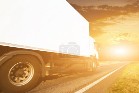 Truck on highway at sunset