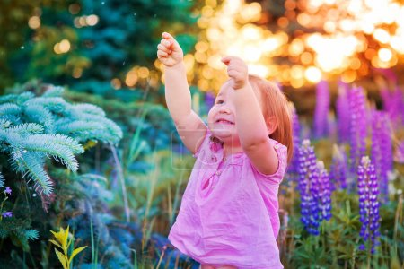 Photo for Portrait of little girl in a field of flowers at summer evening - Royalty Free Image