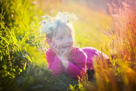 Photo for Cute little girl in flowers wreath laying in a field - Royalty Free Image