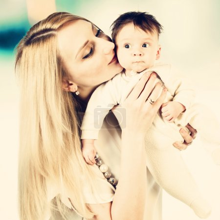 Photo for Portrait of young mother kissing her little child - Royalty Free Image