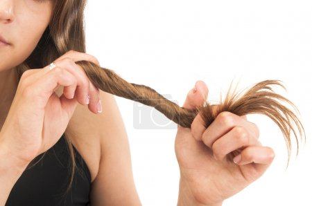 Photo pour Concept de la saine croissance des cheveux. Portrait de la belle jeune femme tenant ses longs cheveux sur fond blanc - image libre de droit