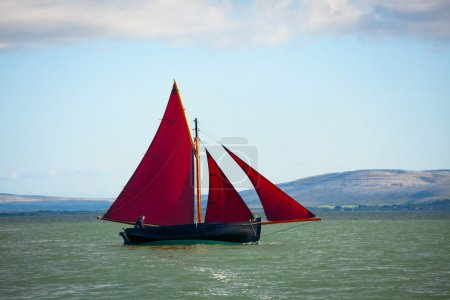 Traditional wooden boa Galway Hooker, with red sai...
