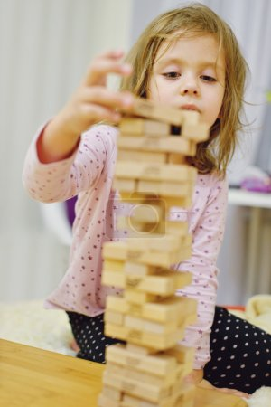 Photo for Little girl with wooden blocks playing at home - Royalty Free Image